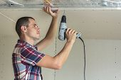 Young Man In Usual Clothing And Work Gloves Fixing Drywall Suspended Ceiling To Metal Frame Using El poster