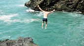 Man Jumps From A Cliff Into The Sea In Slow Motion. Having Fun On Summer Vacation. poster