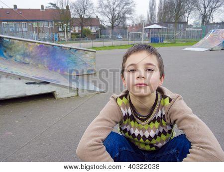 Cute Boy Sitting In Playground