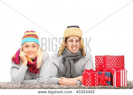 A happy couple with hats and neckwears lying on a carpet near presents isolated on white background