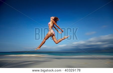 Woman jumping on a white sandy beach at sunny day with motion blurred background