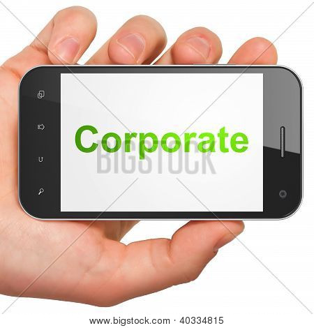 Hand holding smartphone with word Corporate on display. Generic
