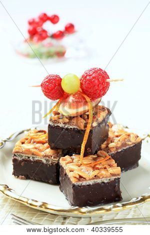 cubes of chocolate cake with seeds decorated with fruit skewer