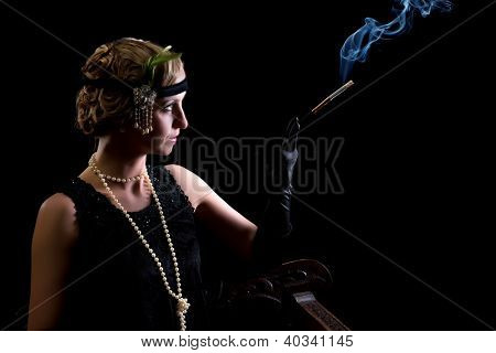 Cigarette smoking lady dressed in flapper dress in twenties style