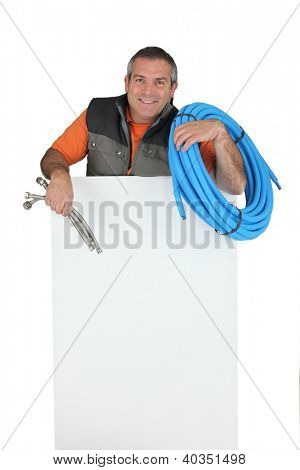 Plumber with materials and a board left blank for your message