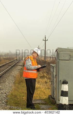 Empleado del ferrocarril escribe cerca de la caja eléctrica