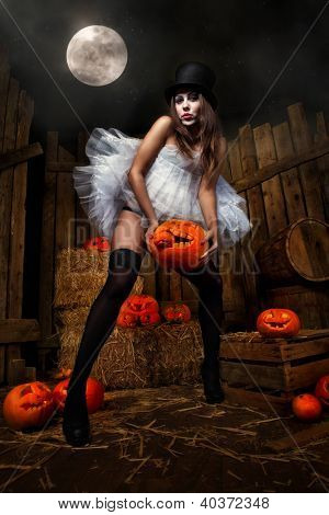 Beautiful sexy woman with halloween pumpkin against wooden background and moon