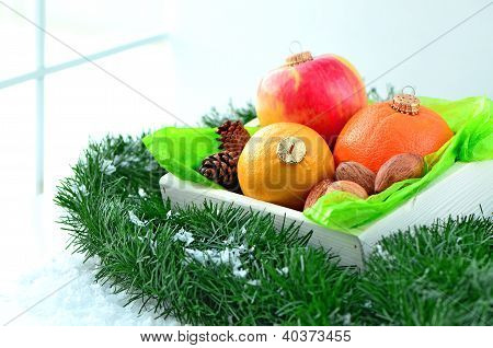 fruits like a christmas ornaments in a white wooden box