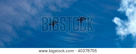 Two F-18 Hornet Figher Jets Over A Blue Sky