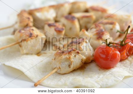 Chicken souvlaki with cherry tomato on a flatbread