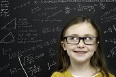 foto of cheeky  - Smart young girl wearing a yellow jumper and glasses stood infront of a blackboard with mathematical equations written in chalk - JPG