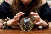 stock photo of divine  - Young fortune teller indicated something in a ball - JPG