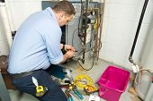 foto of plumber  - Plumber fixing gas furnace using electric and plumbing tools - JPG