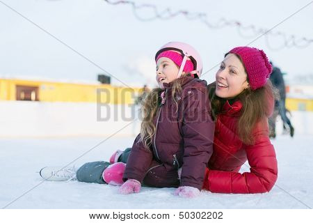 Happy mother and daughter sitting on the outdoor skating rink in winter