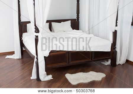 Wooden canopy bed and a white hide on the floor in a light room