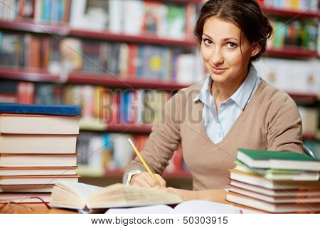 Portrait of clever student working in college library