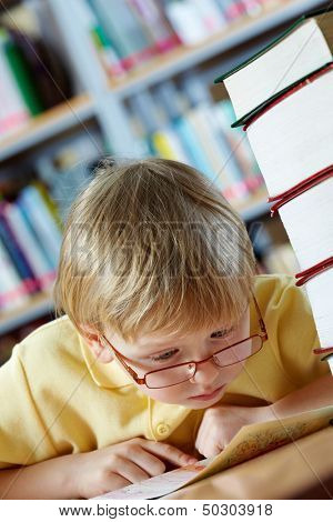 Portrait of surprised boy looking at map in library