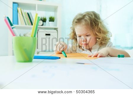 Diligent preschool child drawing at home