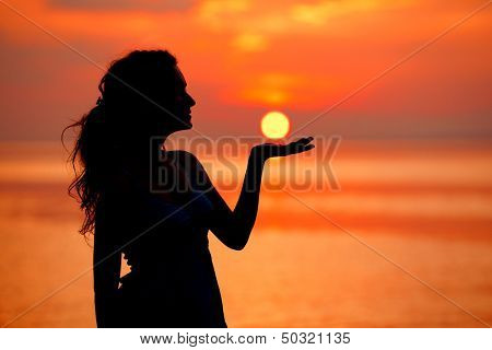 Happy free Woman enjoying in Sea Sunset. Silhouetted against the sunset, sunrise. Sun on the palm