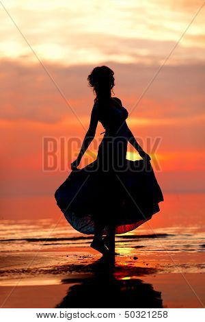 Happy free Woman enjoying in Sea Sunset. Silhouetted against the sunset, sunrise