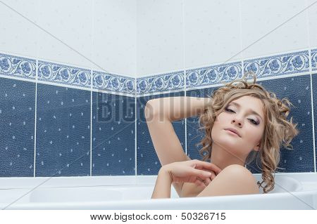 Portrait of languid young woman lying in bath