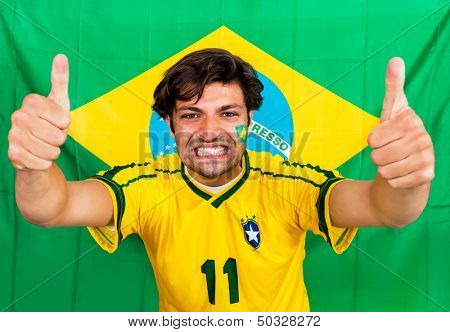 Brazilian sports fan, supporting his national team cheering with his outstreched arms and thumbs up in front of a Brazil Flag, wearing the national colors