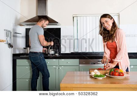 Portrait of young woman cutting vegetables at kitchen counter with man cooking in background
