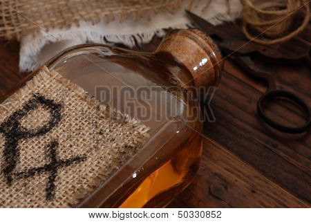 Old fashioned medicine bottle (with handwritten letters on burlap tag), antique scissors, and fabric bandages on rustic wood background.  Low key still life with directional, natural lighting.