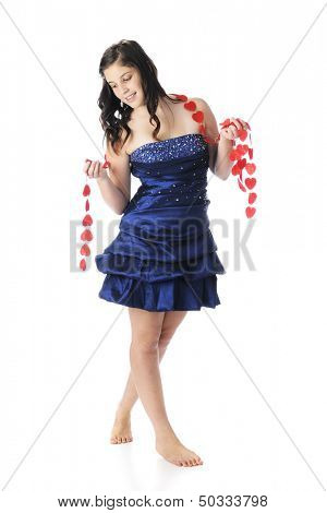 A beautiful, barefoot young teen in a formal dress looking wistfully at a strand of red hearts.  On a white background.