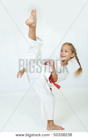 Cheerful athlete in a kimono performs a high kick leg circular