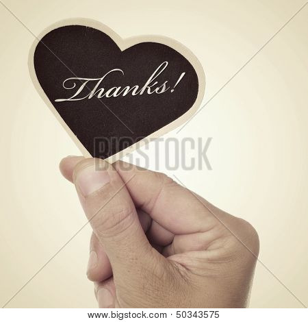 picture of a man hand holding a heart-shaped blackboard with the word thanks written in it, with a retro effect