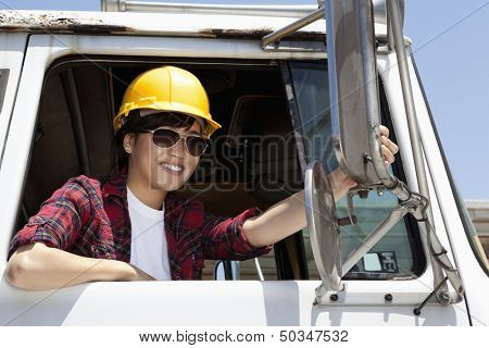 Female industrial worker adjusting mirror while sitting in logging truck