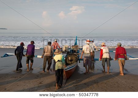 PADANG - AUGUST 25: Fishermen work as a team launch the boat to sea in Padang, West Sumatera, Indonesia on August 25, 2013. Resources from the sea is a major revenue earner.