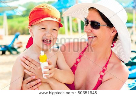 Mom and son on the beach to protect the skin from sun lotion