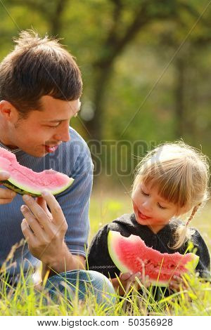 Father And Young Daughter Eat Watermelon In Nature