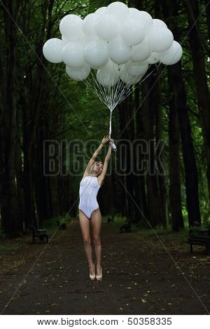 Fantasy. Nostalgic Svelte Woman With Air Balloons On Country Road