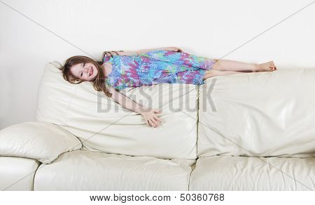 Young Girl In Fun Pose On Settee - Home Interior