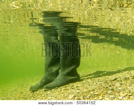 Rubber Boots Or Gumboots Underwater On Sand Ground