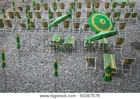 Green And Yellow Beach Umbrellas And Deckchairs On Stony Beach in Camogli