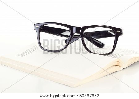 Black Glasses On Open Book