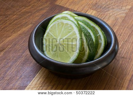 Lime slices in brown bowl