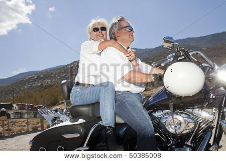 Senior couple riding a motorcycle together in a rural landscape