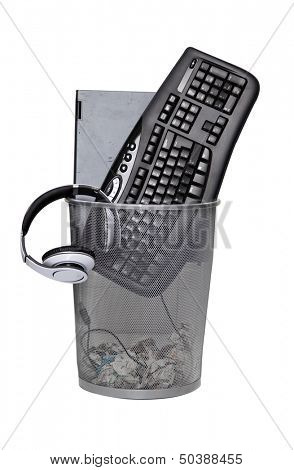Computer keyboard and headphones in wastebasket against white background