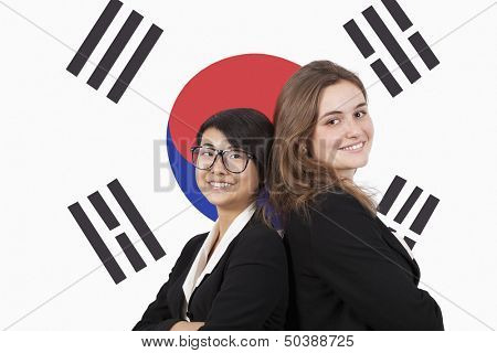Portrait of young multiethnic businesswomen smiling over Korean flag