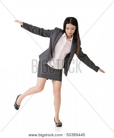 Young asian business woman standing on precipice, trying to balance. Full length portrait. Isolated on the white background.