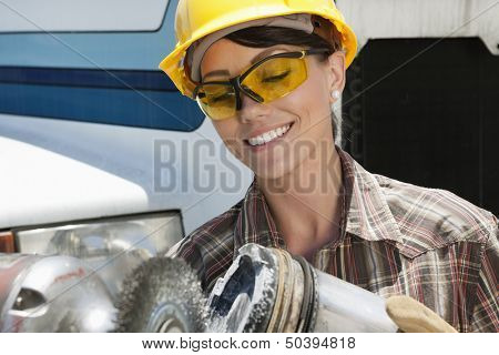 Mid adult female industrial worker buffing a truck engine cylinder