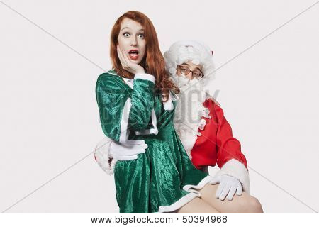 Portrait of Santa touching woman inappropriately against gray background