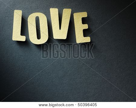 The word Love in cut out paper letters on paper background