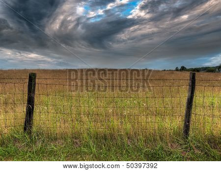 Fenceline And Dramatic Clouds