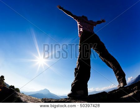 Man opens his arms in the sunshine against blue sky. Concept: freedom, success, energy, vitality.